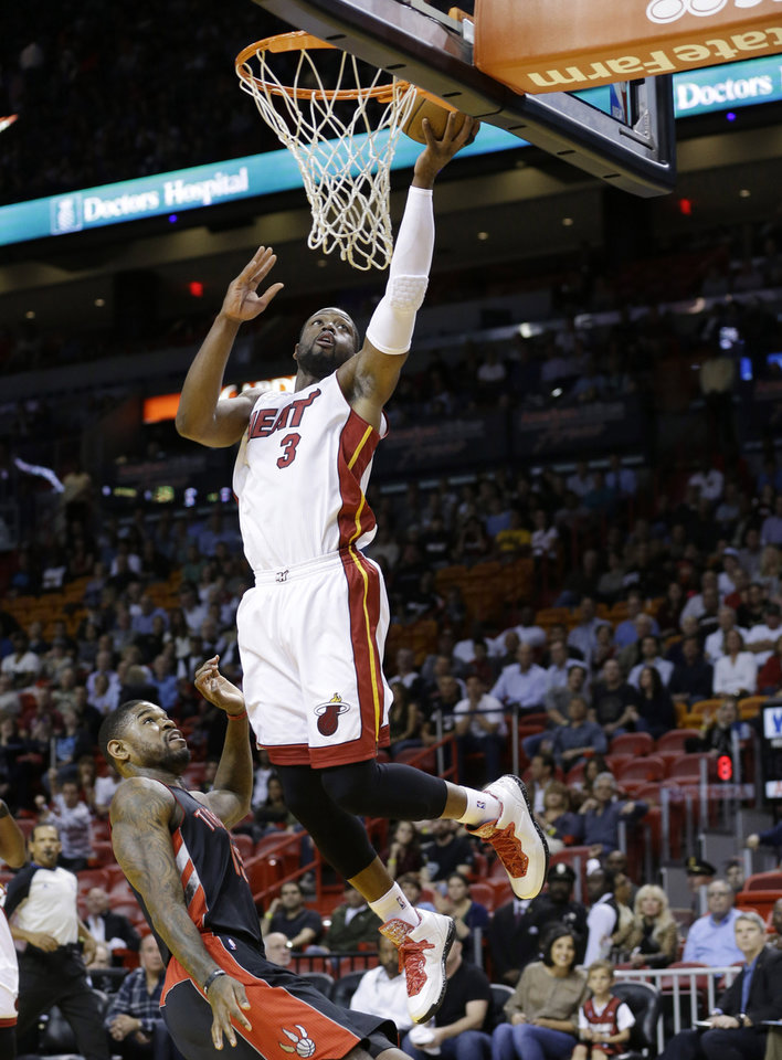 Miami Heat guard Dwyane Wade (3) shoots against Toronto Raptors forward Amir Johnson during the first half of an NBA basketball game on Wednesday, Jan. 23, 2013, in Miami. (AP Photo/Wilfredo Lee)