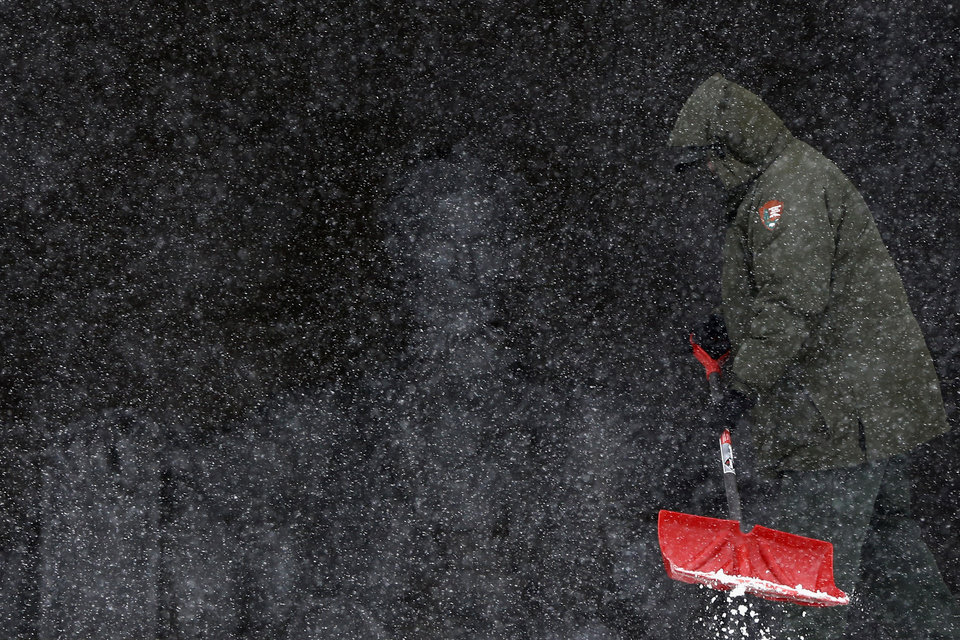 Photo - National Park Service employee Eric Tolliver shovels snow and ice at the Lincoln Memorial as snow falls in Washington, Monday, March 3, 2014. The National Weather Service has issued a Winter Storm Warning for the greater Washington Metropolitan region, prompting area schools and the federal government to close for the wintry weather. (AP Photo/Charles Dharapak)