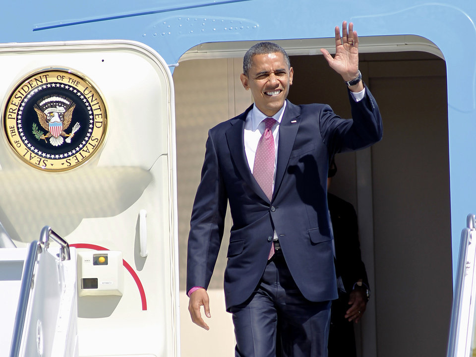 Photo -   President Barack Obama waves after arriving on Air Force One at West Palm Beach Airport in West Palm Beach, Fla., Monday, Oct. 22, 2012, ahead of his final debate tonight against Republican presidential candidate, former Massachusetts Gov. Mitt Romney at Lynn University in Boca Raton, Fla. (AP Photo/Terry Renna)
