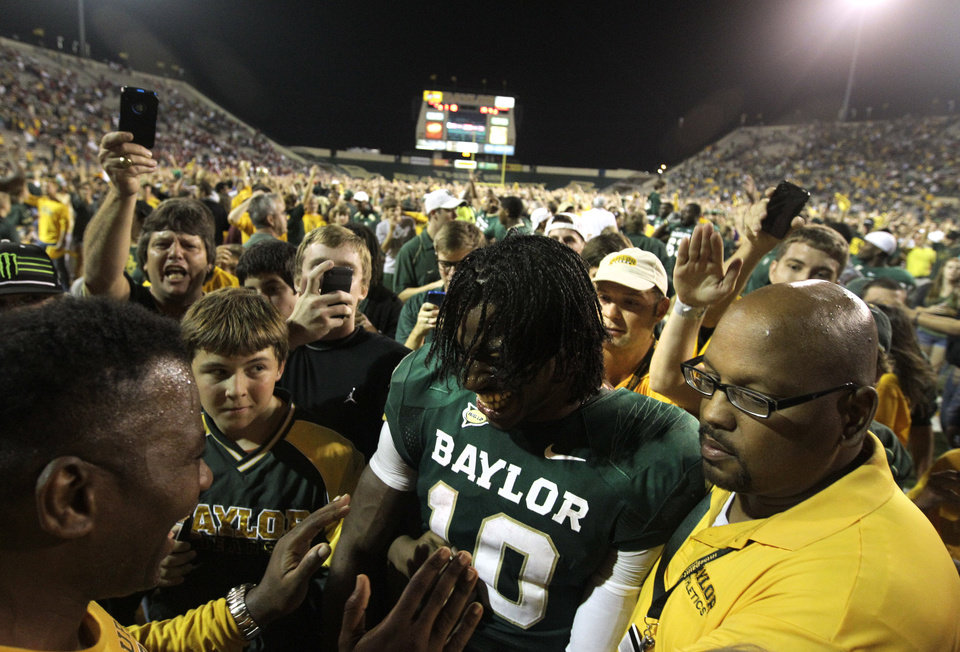 Photo - Baylor quarterback Robert Griffin III (10) is surrounded by fans that rushed the field and security as he is escorted off the field following their 45-38 win over Oklahoma in an NCAA college football game Saturday, Nov. 19, 2011, in Waco, Texas. (AP Photo/Tony Gutierrez)