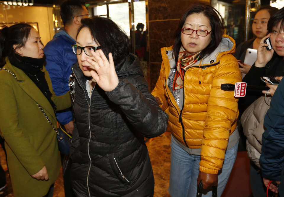 Photo - Chinese women walk through journalists as they arrive at a hotel which is prepared for relatives or friends of passengers aboard a missing Malaysia Airlines airplane in Beijing Saturday, March 8, 2014. Search teams across Southeast Asia scrambled on Saturday to find a Malaysia Airlines Boeing 777 with 239 people on board that disappeared from air traffic control screens over waters between Malaysia and Vietnam early that morning. (AP Photo/Vincent Thian)