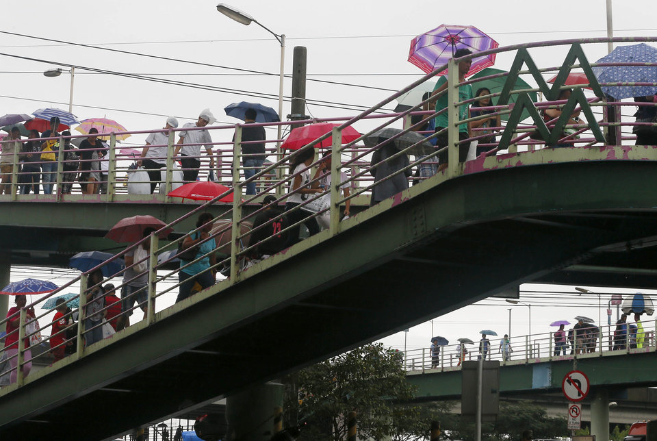 Photo - People carry umbrellas as they walk on pedestrian bridges during a slight rain brought about by typhoon Melor (local name