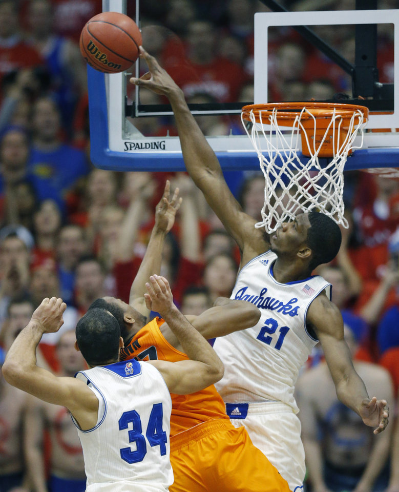 Photo - Kansas center Joel Embiid (21) blocks a shot by Oklahoma State guard Markel Brown (22) during the first half of an NCAA college basketball game at Allen Fieldhouse in Lawrence, Kan., Saturday, Jan. 18, 2014. (AP Photo/Orlin Wagner)