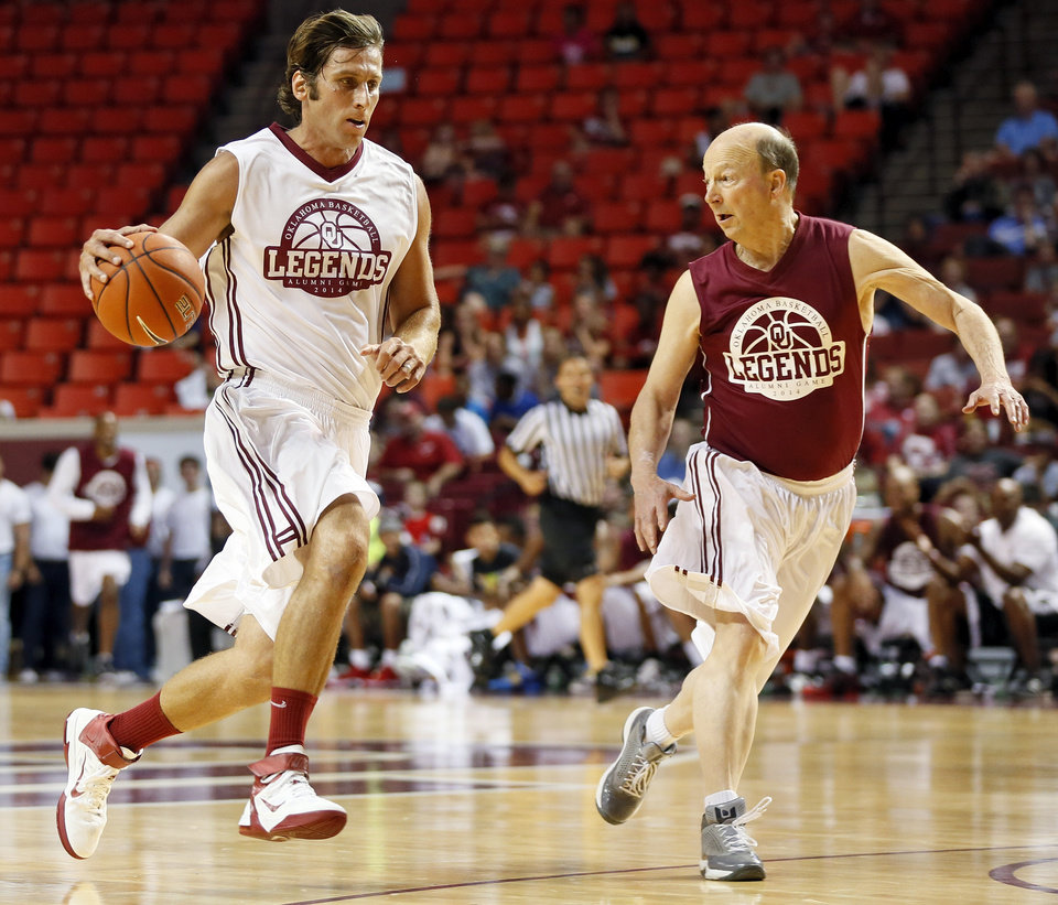 Photo - Jozsef Szendrei dribbles against Bill Dutcher during the OU Legends Alumni Game in Lloyd Noble Center in Norman, Okla., Saturday, Aug. 23, 2014. The game is part of the Sooner Basketball Family Weekend. Photo by Nate Billings, The Oklahoman