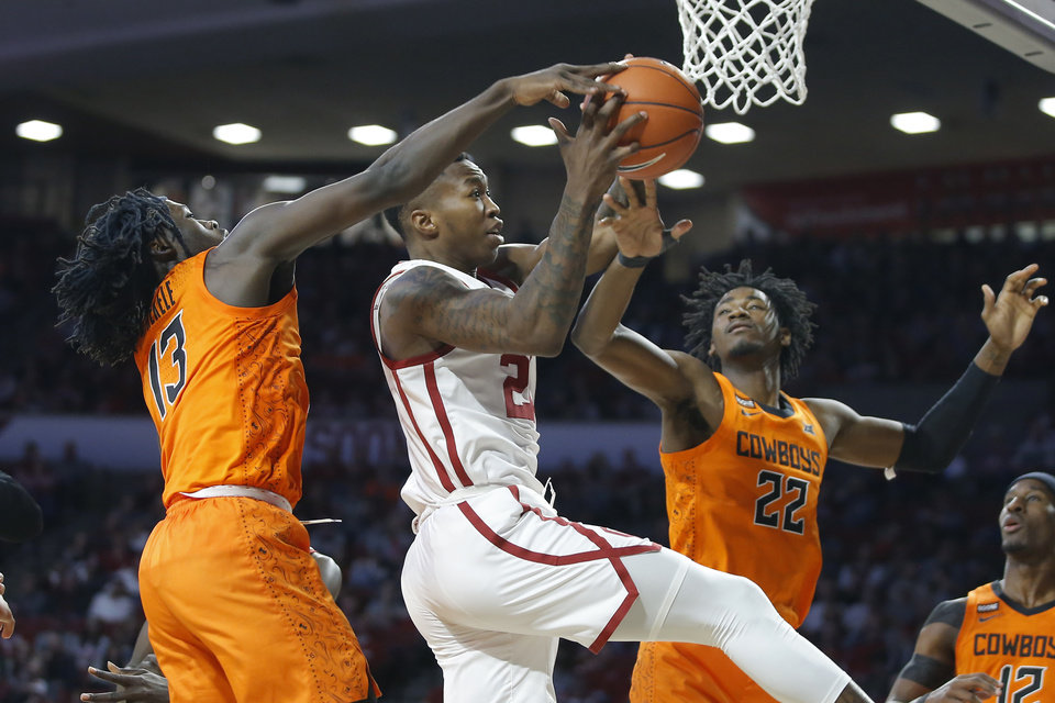 Photo - Oklahoma's Kristian Doolittle (21) goes to the basket between Oklahoma State's Isaac Likekele (13) and Kalib Boone (22) during a Bedlam college basketball game between the University Oklahoma Sooners (OU) and the Oklahoma State Cowboys (OSU) at the Lloyd Noble Center in Norman, Okla., Saturday, Feb. 1, 2020. Oklahoma won 82-69. [Bryan Terry/The Oklahoman]