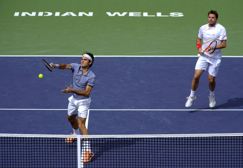 Photo - Roger Federer returns a volley as he and doubles partner Stanislas Wawrinka, both of Switzerland, play Rohan Bopanna, of India, and Aisam-Ul-Haq Qureshi, of Pakistan, at the BNP Paribas Open tennis tournament Friday, March 7, 2014, in Indian Wells, Calif. (AP Photo/Mark J. Terrill)
