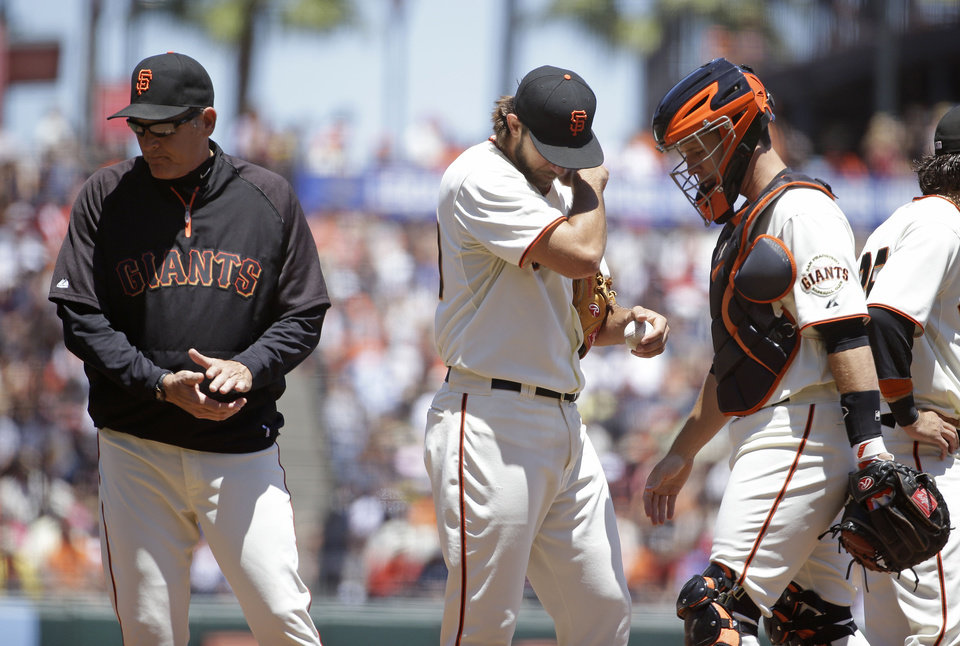Photo - From left to right, San Francisco Giants pitching coach Dave Righetti, starting pitcher Madison Bumgarner and catcher Buster Posey stand on the mound after a talk in the fourth inning of a baseball game against the St. Louis Cardinals, Thursday, July 3, 2014, in San Francisco. (AP Photo/Eric Risberg)