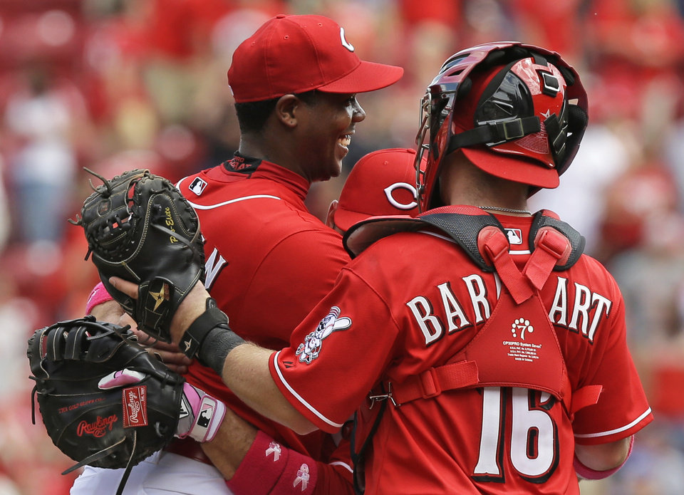 Photo - Cincinnati Reds relief pitcher Aroldis Chapman, left, is hugged by Joey Votto and Tucker Barnhart (16) after Chapman earned his first save of the season in the Reds 4-1 win over the Colorado Rockies in a baseball game, Sunday, May 11, 2014, in Cincinnati. Chapman was making his first appearance since being hit in the head with a line drive in spring training. (AP Photo/Al Behrman)