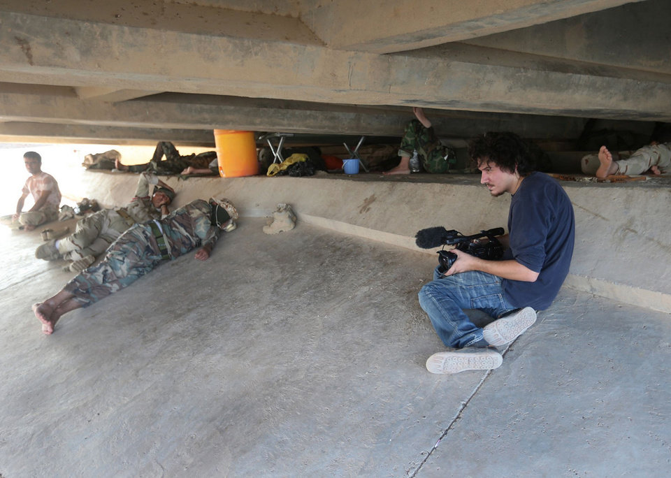 Photo - This July 1, 2014 photo shows Associated Press video journalist Simone Camilli at work filming Kurdish Peshmerga fighters under a bridge near the front line with militants from the Islamic state group, in Mariam Bek village, between the northern cities of Tikrit and Kirkuk, Iraq. Camilli, 35, was killed in an ordnance explosion in the Gaza Strip, on Wednesday, Aug. 13, 2014 together with Palestinian translator Ali Shehda Abu Afash and three members of the Gaza police. Police said four other people were seriously injured, including AP photographer Hatem Moussa.(AP Photo/Hussein Malla)