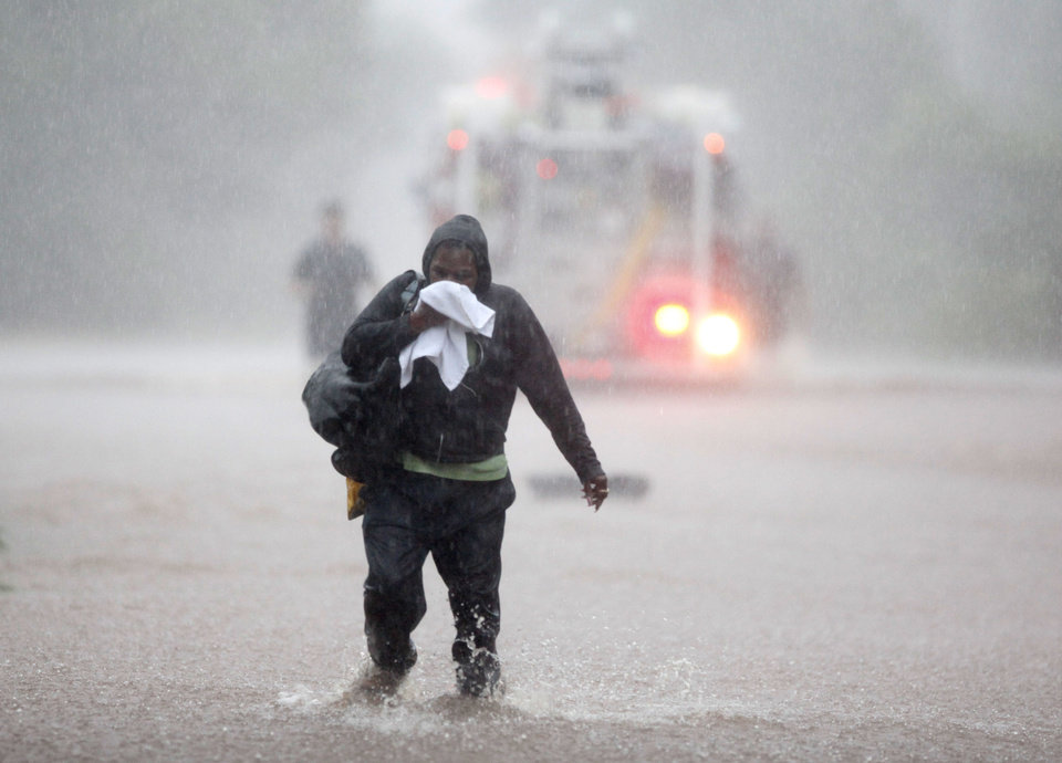 Photo - A motorist walks away from her stalled vehicle as Oklahoma City firefighters work to rescue other stalled vehicles on Hefner Road between Kelly Avenue and the Broadway Extension in Oklahoma City, OK, Monday, June 14, 2010. By Paul Hellstern, The Oklahoman