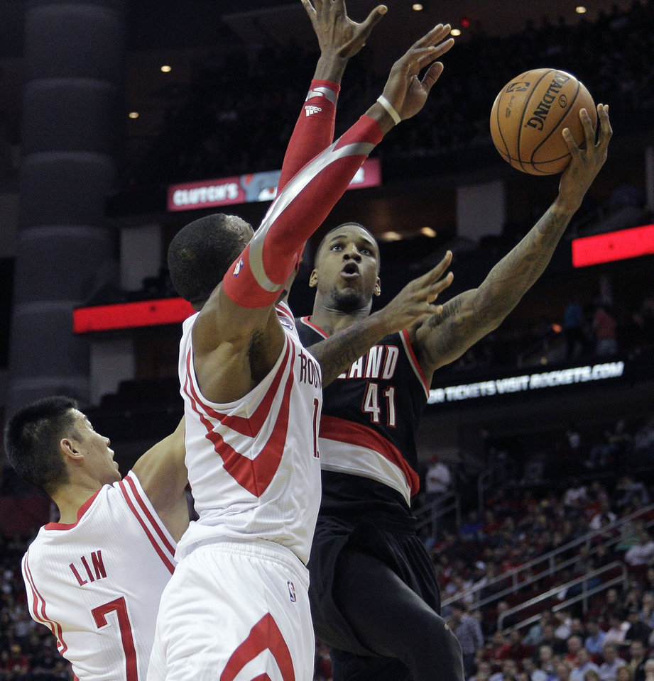 Photo - Portland Trail Blazers forward Thomas Robinson (41) drives to the basket past Houston Rockets' Dwight Howard (12) and Jeremy Lin (7) during the first half of an NBA basketball game, Monday, Jan. 20, 2014, in Houston. (AP Photo/Bob Levey)