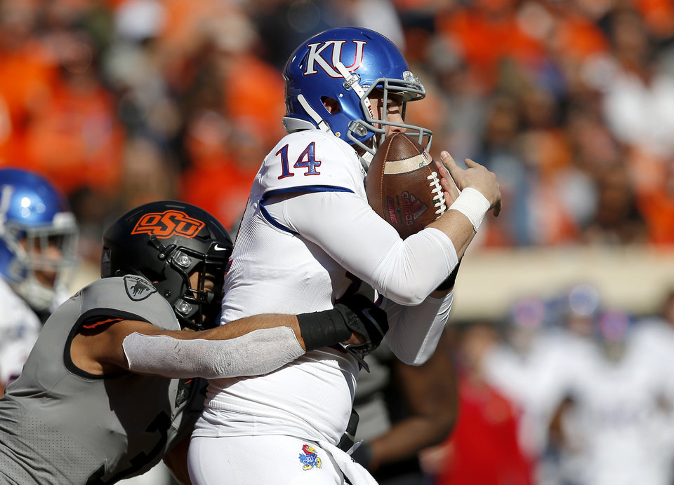Photo - Oklahoma State's Tre Sterling (3) sacks Kansas's Manny Miles (14) in the third quarter during the college football game between the Oklahoma State University Cowboys and the Kansas Jayhawks at Boone Pickens Stadium in Stillwater, Okla., Saturday, Nov. 16, 2019. OSU won 31-13. [Sarah Phipps/The Oklahoman]