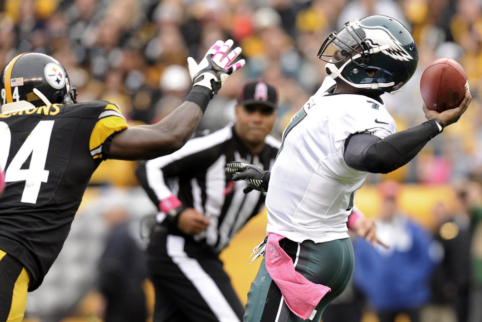 Philadelphia Eagles quarterback Michael Vick, right, looks to pass as Pittsburgh Steelers inside linebacker Lawrence Timmons, left, applies pressure in the first quarter of an NFL football game on Sunday, Oct. 7, 2012, in Pittsburgh. (AP Photo/Don Wright)