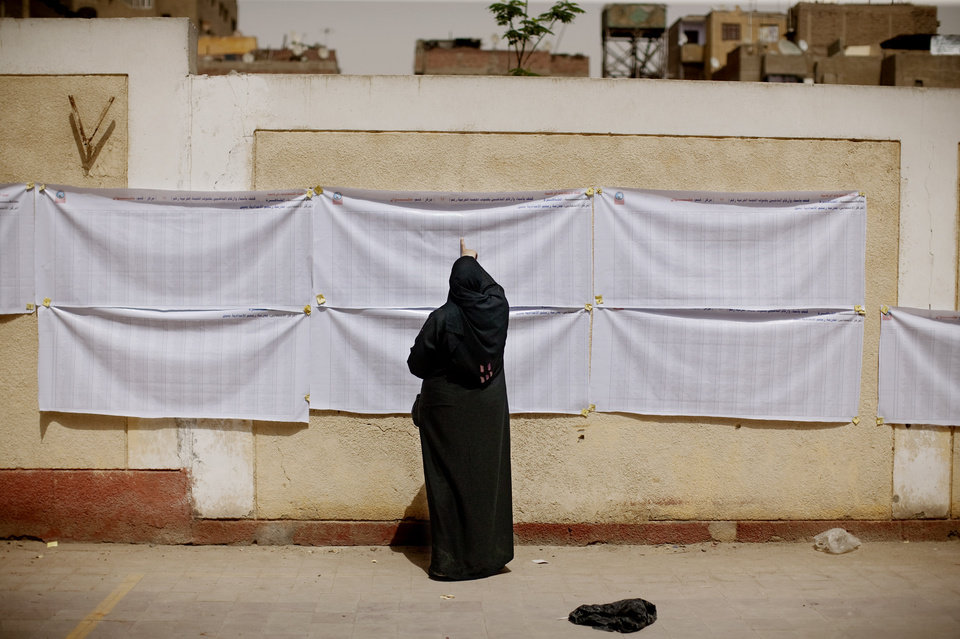 Photo -   An Egyptian woman searches for her name on a registration list outside a polling station in Helwan, a southern suburb of Cario, Egypt on Wednesday, May 23, 2012. On Wednesday morning, Egypt commenced two days of presidential voting after 16 months of interim rule by the Supreme Council of Armed Forces. This election is the first free and fair presidential race since the ouster of former President Hosni Mubarak. (AP Photo/Pete Muller)