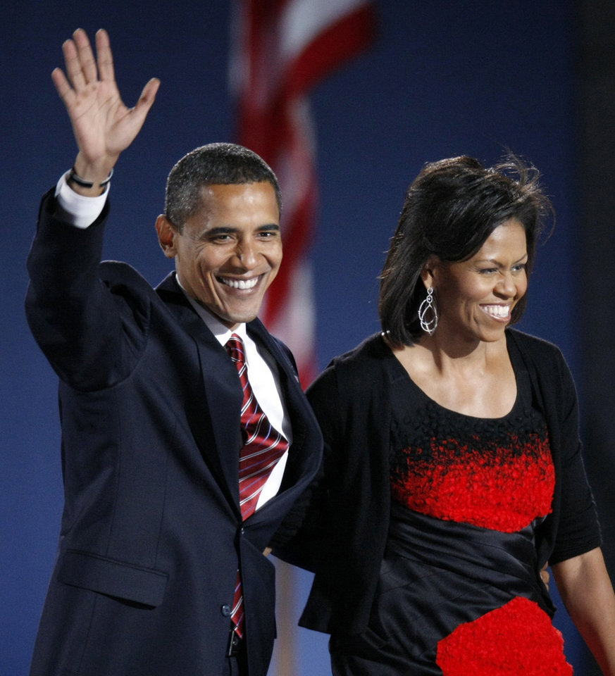 Photo - FILE -  This Nov. 4, 2008 file photo shows then-President-elect Barack Obama and his wife Michelle Obama, wearing a Narciso Rodriguez dress, acknowledge the crowd after he delivered his victory speech at his election night party at Grant Park in Chicago. Fashion designer Narcisco Rodriguez will receive a National Design Award this year from the Smithsonian's Cooper-Hewitt National Design Museum, along with 10 other top names in design. Rodriguez designed the black and red dress worn by first lady Michelle Obama in Chicago on election night in 2008. The dress recently went on display at the National Archives to represent her signature style. Earlier, Rodriguez designed Carolyn Bessette's wedding dress for her 1996 marriage to John F. Kennedy Jr. (AP Photo/Pablo Martinez Monsivais, File)