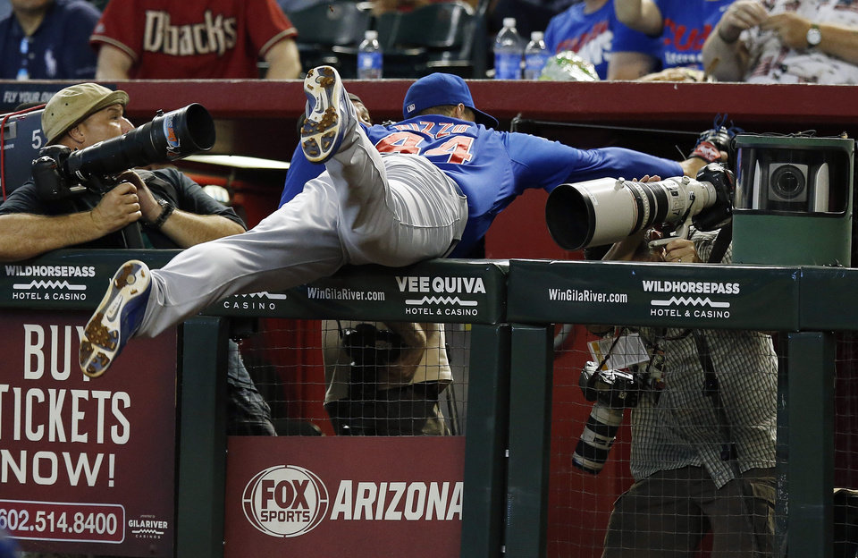 Photo - Chicago Cubs' Anthony Rizzo makes a diving catch into the photo well on a foul ball hit by Arizona Diamondbacks' Aaron Hill during the sixth inning of a baseball game on Sunday, July 20, 2014, in Phoenix. (AP Photo/Ross D. Franklin)