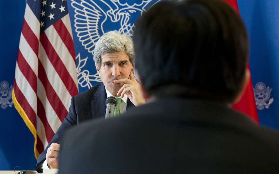 Photo - U.S. Secretary of State John Kerry, rear, listens to a question during a discussion with Chinese bloggers on a number of issues, including internet freedom, Chinese territorial disputes with Japan, North Korea, and human rights, on Saturday, Feb. 15, 2014, in Beijing, China. (AP Photo/Evan Vucci, Pool)