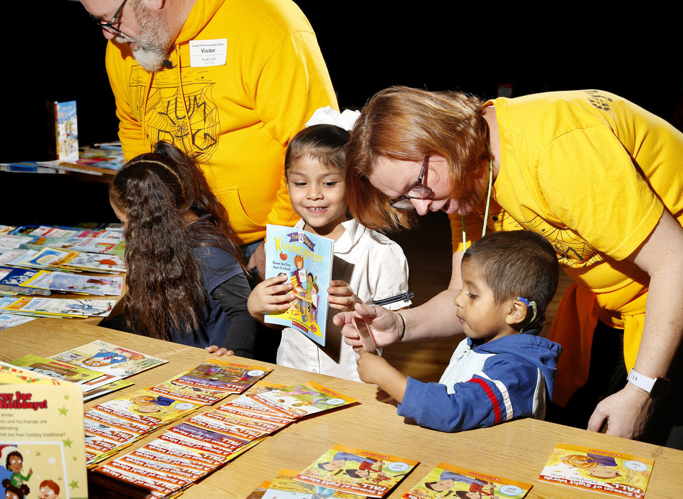 Photo -  Kathleen Liner and her husband, Scott, help prekindergarten students select books. The Capitol Hill Elementary School teacher and her husband are owners of a popular food truck (Yum Pig). They donated 50 cents from the sale of every Cowboy sandwich to buy books for all 545 students at the school. [Photo by Jim Beckel, The Oklahoman.]