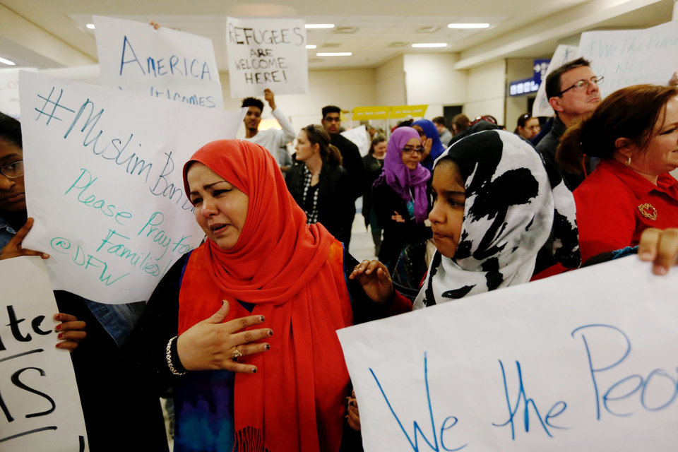 Photo - A woman, left, who did not want to be identified reacts after hearing news that her mother may not be released from immigration at DFW airport, Saturday, Jan. 28, 2017. President Donald Trump signed an executive order barring muslims from certain countries from entering the Untied States. (Brandon Wade/Star-Telegram via AP)