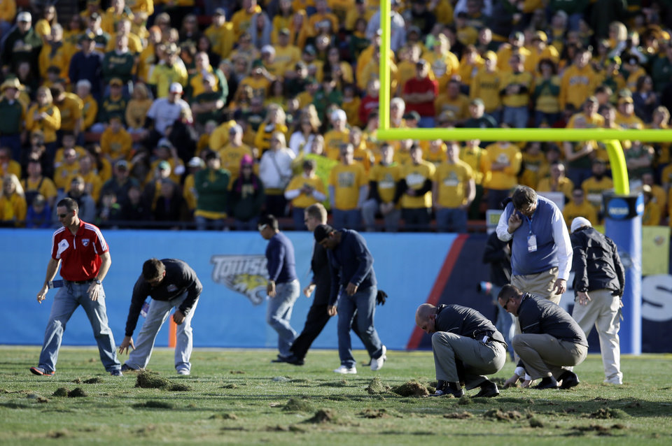Photo - Stadium officials and volunteers replaces chunks of turf on the field in the second half of the FCS championship NCAA college football game between North Dakota State and Towson, Saturday, Jan. 4, 2014, in Frisco, Texas. During each timeout, groups of workers and volunteers patted down chunks of turf that were coming up during play. NDSU won 35-7. (AP Photo/Tony Gutierrez)