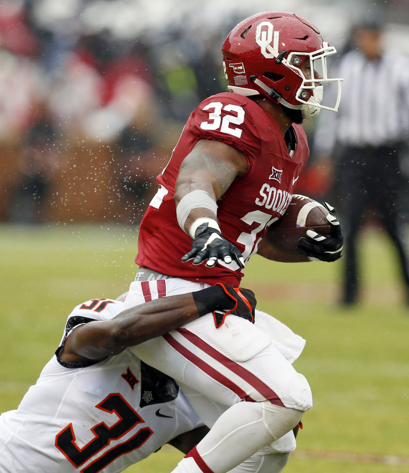 Photo - Oklahoma State's Tre Flowers (31) tackles Oklahoma's Samaje Perine (32) in the first quarter during the Bedlam college football game between the Oklahoma Sooners (OU) and the Oklahoma State Cowboys (OSU) at Gaylord Family - Oklahoma Memorial Stadium in Norman, Okla., Saturday, Dec. 3, 2016. Photo by Nate Billings, The Oklahoman