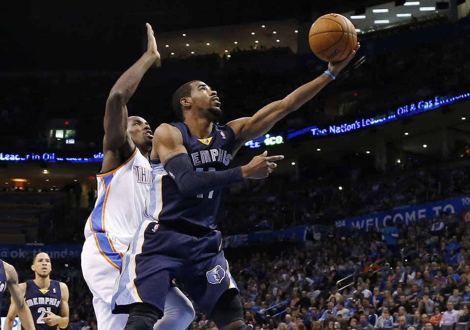 Photo - Memphis Grizzlies guard Mike Conley (11) shoots in front of Oklahoma City Thunder forward Serge Ibaka during the first quarter of an NBA basketball game in Oklahoma City, Friday, Feb. 28, 2014. (AP Photo/Sue Ogrocki)