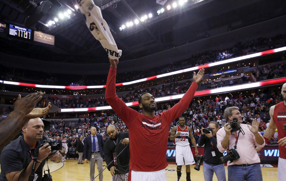 Photo - Washington Wizards guard John Wall, center, celebrates after an NBA basketball game against the Boston Celtics on Wednesday, April 2, 2014, in Washington. The Wizards won 118-92, and clinched a playoff berth. (AP Photo/Alex Brandon)