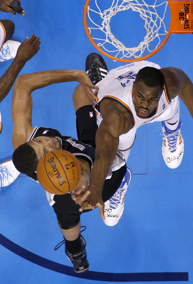 Photo - Oklahoma City's Serge Ibaka (9) blocks the shot of San Antonio's Tim Duncan (21) during Game 3 of the Western Conference Finals in the NBA playoffs between the Oklahoma City Thunder and the San Antonio Spurs at Chesapeake Energy Arena in Oklahoma City, Sunday, May 25, 2014. Photo by Bryan Terry, The Oklahoman