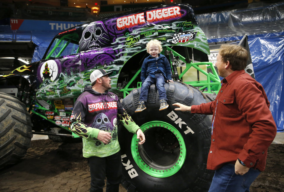 Photo - Ryker Ammons, 4, of Yukon, Okla.,  sits on the tire of Grave Digger as driver, Brandon Vinson, and his dad Ryan Ammons talk with him during a special meet and greet at Chesapeake Energy Arena in Oklahoma City, Friday, Feb. 14, 2020.  [Sarah Phipps/The Oklahoman]