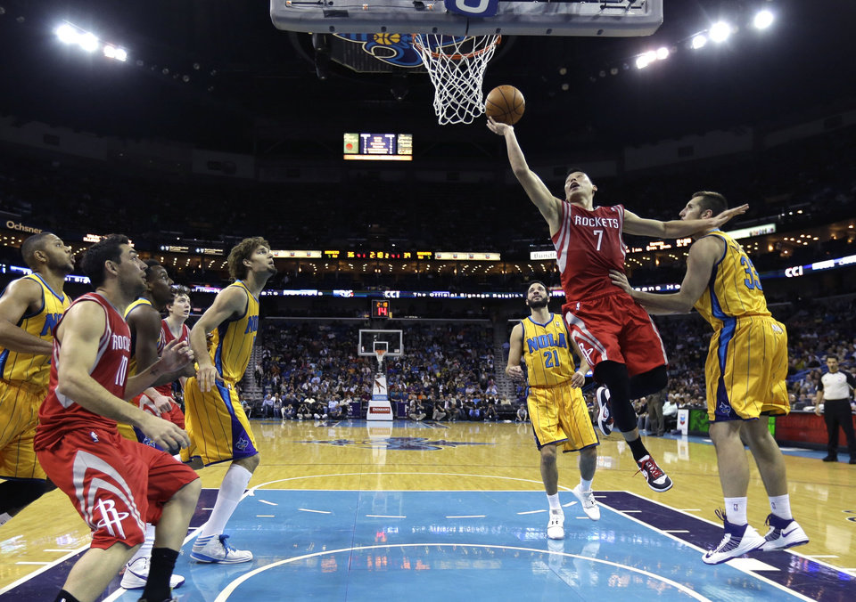 Photo - Houston Rockets guard Jeremy Lin (7) drives to the basket against New Orleans Hornets forward Ryan Anderson (33) in the first half of an NBA basketball game in New Orleans, Friday, Jan. 25, 2013. (AP Photo/Gerald Herbert)