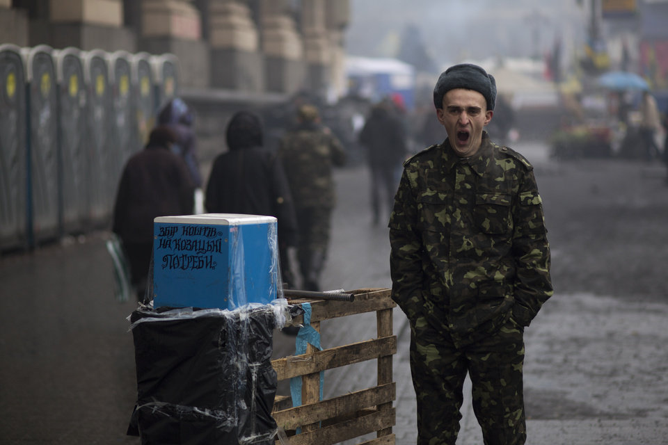Photo - A Ukrainian man wearing camouflage uniform yawns as he asks for donations to support the Ukrainian military with the slogan on box reading