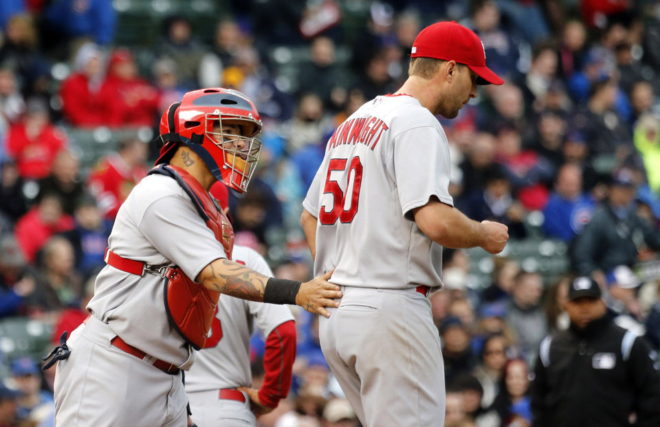 Photo - St. Louis Cardinals catcher Yadier Molina, left, pats starting pitcher Adam Wainwright during the fifth inning of a baseball game against the Chicago Cubs, Friday, May 2, 2014, in Chicago. (AP Photo/Charles Rex Arbogast)