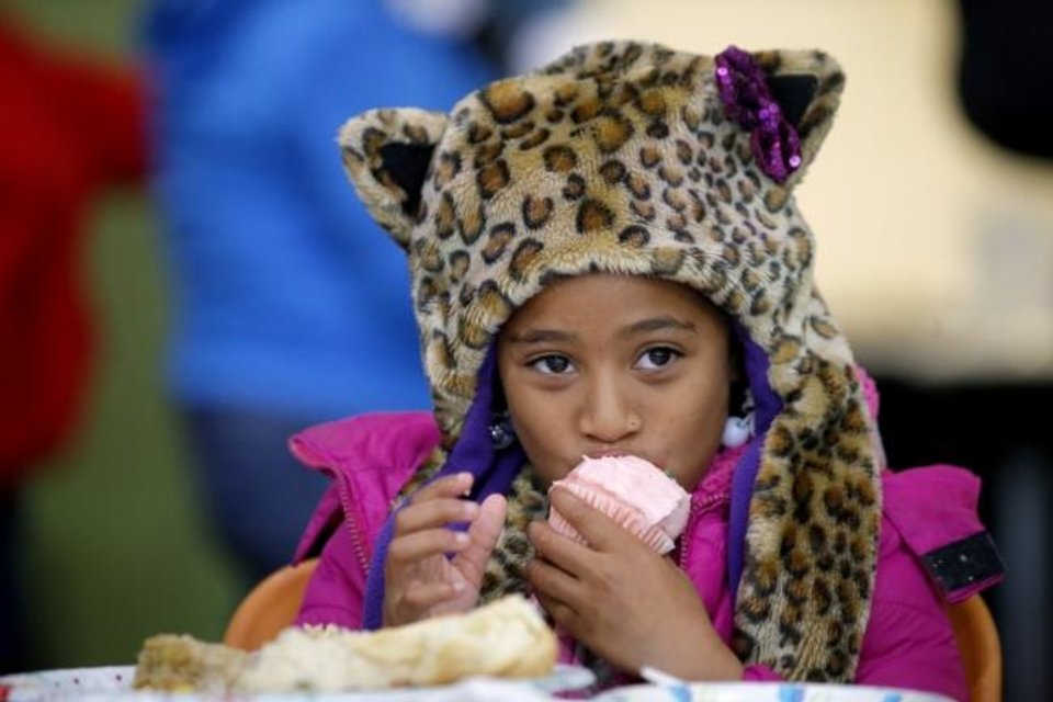 Photo -  Noamy Flloyd, 7, eats a cupcake during the Homeless Alliance Thanksgiving dinner Wednesday at the WestTown day shelter in Oklahoma City. [Bryan Terry/The Oklahoman]