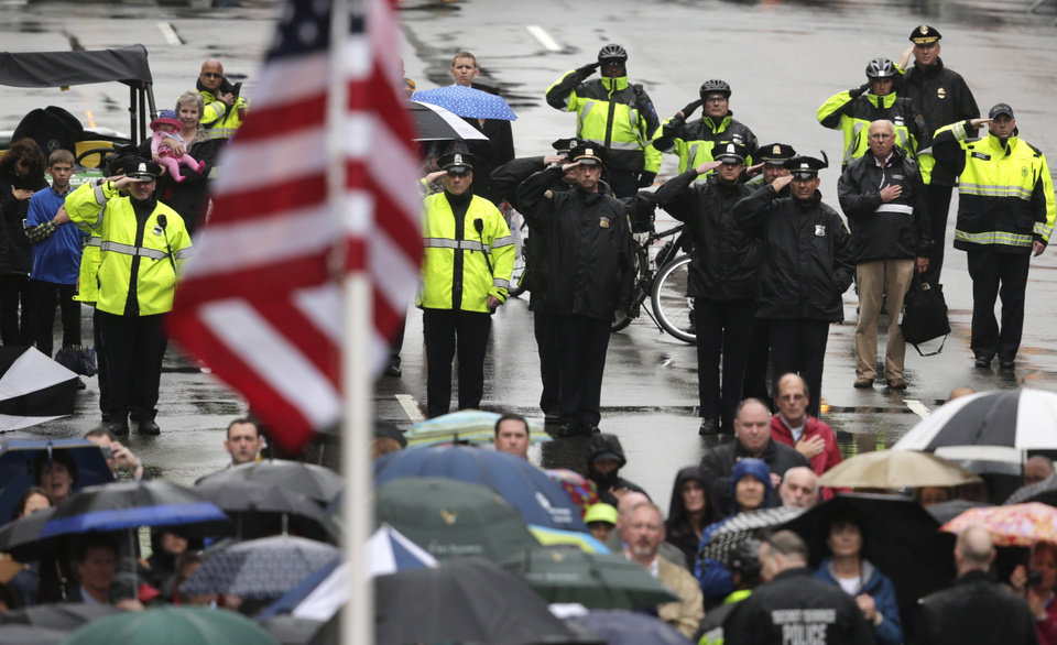 Photo - Police salute as a U.S. flag is raised at the finish line during a tribute in honor of the one year anniversary of the Boston Marathon bombings, Tuesday, April 15, 2014 in Boston. (AP Photo/Charles Krupa)