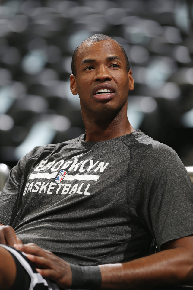 Photo - Brooklyn Nets center Jason Collins rests in a courtside seat after warning up for the Nets' NBA basketball game against the Denver Nuggets in Denver on Thursday, Feb. 27, 2014. (AP Photo/David Zalubowski)