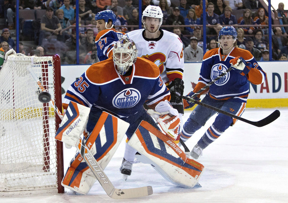 Photo - Calgary Flames' Paul Byron (32) looks for the rebound off of Edmonton Oilers goalie Viktor Fasth (35) as Boyd Gordon (27) and Jeff Petry (2) defend during the first period of an NHL hockey game Saturday, March 22, 2014, in Edmonton, Alberta. (AP Photo/The Canadian Press, Jason Franson)