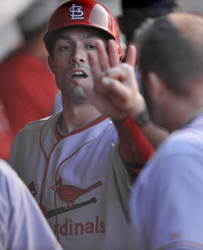 St. Louis Cardinals' Randal Grichuk celebrates with teammates in the dugout after scoring on a Mark Ellis double during the second inning of baseball game against the Chicago Cubs in Chicago, Sunday, May 4, 2014. (AP Photo/Paul Beaty)