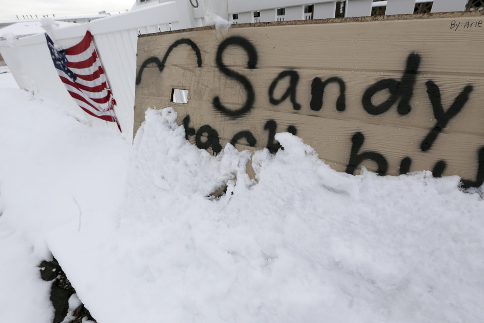 Photo -   A message about Superstorm Sandy on a wooden board is half covered by snow the morning after a nor'easter rolled through the already damaged beachfront town of Point Pleasant, N.J., Thursday, Nov. 8, 2012. (AP Photo/Julio Cortez)