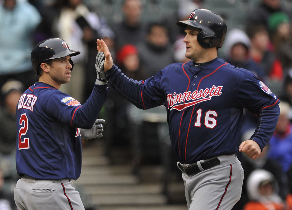 Photo - Minnesota Twins' Josh Willingham (16), and Brian Dozier (2), celebrate at home plate after both scoring on a 3-RBI double hit by Chris Colabello during the third inning of an baseball game against the Chicago White Sox in Chicago, Thursday, April 3, 2014. (AP Photo/Paul Beaty)