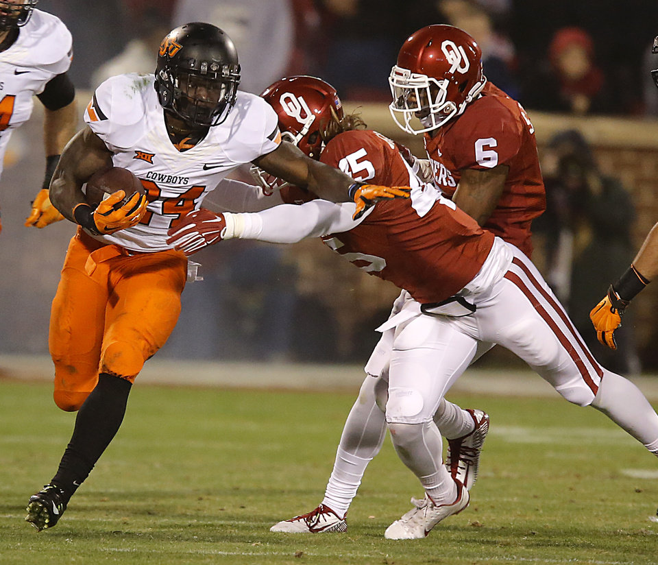 Photo - Oklahoma State's Tyreek Hill (24) runs past Oklahoma's Caleb Gastelum (45) during a Bedlam college football game between the University of Oklahoma Sooners (OU) and the Oklahoma State University Cowboys (OSU) at the Gaylord Family Oklahoma Memorial Stadium in Norman, Okla. on Saturday, Dec. 6, 2014. Photo by Chris Landsberger, The Oklahoman