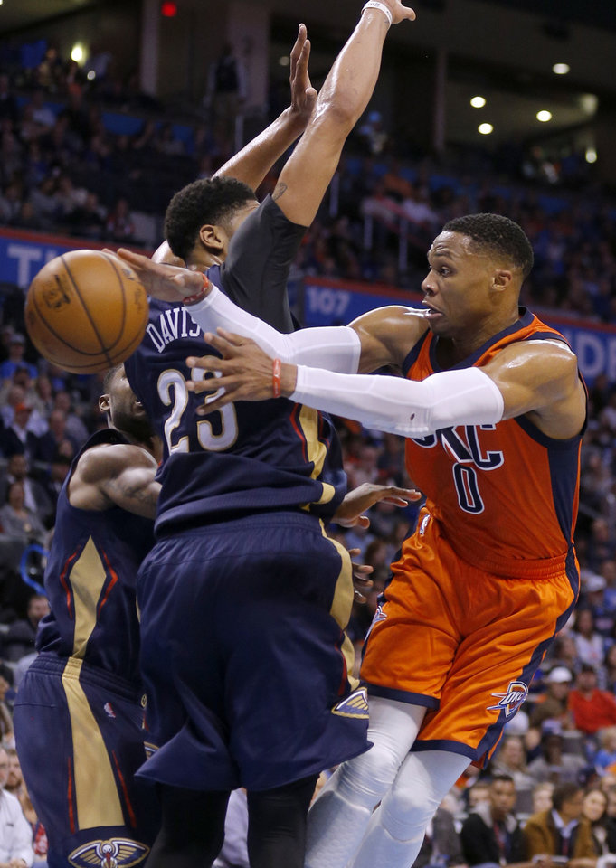 Photo - Oklahoma City's Russell Westbrook (0) passes the ball around New Orleans' Anthony Davis (23) during the NBA game between the Oklahoma City Thunder and the New Orleans Pelicans at the Chesapeake Energy Arena,  Sunday, Dec. 4, 2016. Photo by Sarah Phipps, The Oklahoman