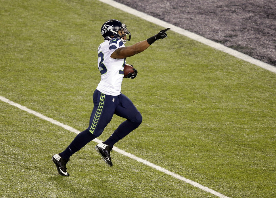 Photo - Seattle Seahawks' Malcolm Smith (53) runs back an interception for a touchdown during the first half of the NFL Super Bowl XLVIII football game against the Denver Broncos Sunday, Feb. 2, 2014, in East Rutherford, N.J. (AP Photo/Charlie Riedel)