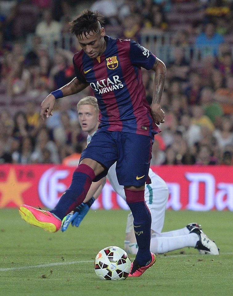 Photo - Barcelona's Neymar, from Brazil, left, scores against Leon's goalkeeper Wiliam Yarbrough at the Camp Nou in Barcelona, Spain, Monday, Aug. 18, 2014. (AP Photo/Manu Fernandez)