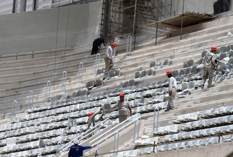 Photo - In this photo released by Portal da Copa, workers install seats at the Arena da Baixada stadium in Curitiba, Brazil, Tuesday, Jan. 21, 2014. FIFA Secretary General Jerome Valcke is giving Brazilian organizers only a few more weeks to show that the stadium in Curitiba will be ready in time for the World Cup. Most of the delay at the venue, which was about 90 percent completed, was blamed on difficulties getting the needed funding for the construction. The stadium is being built mainly by local club Atletico Paranaense. (AP Photo/Portal da Copa, Paulino Menezes)