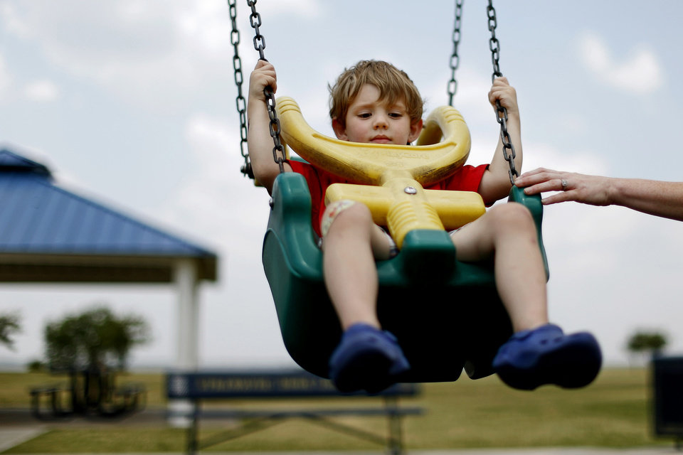 Photo - Oliver Kinman, 3, gets a push from his mother Katie Kinman while on a swing at Lake Hefner on Tuesday in Oklahoma City. Photo by Bryan Terry, The Oklahoman  BRYAN TERRY