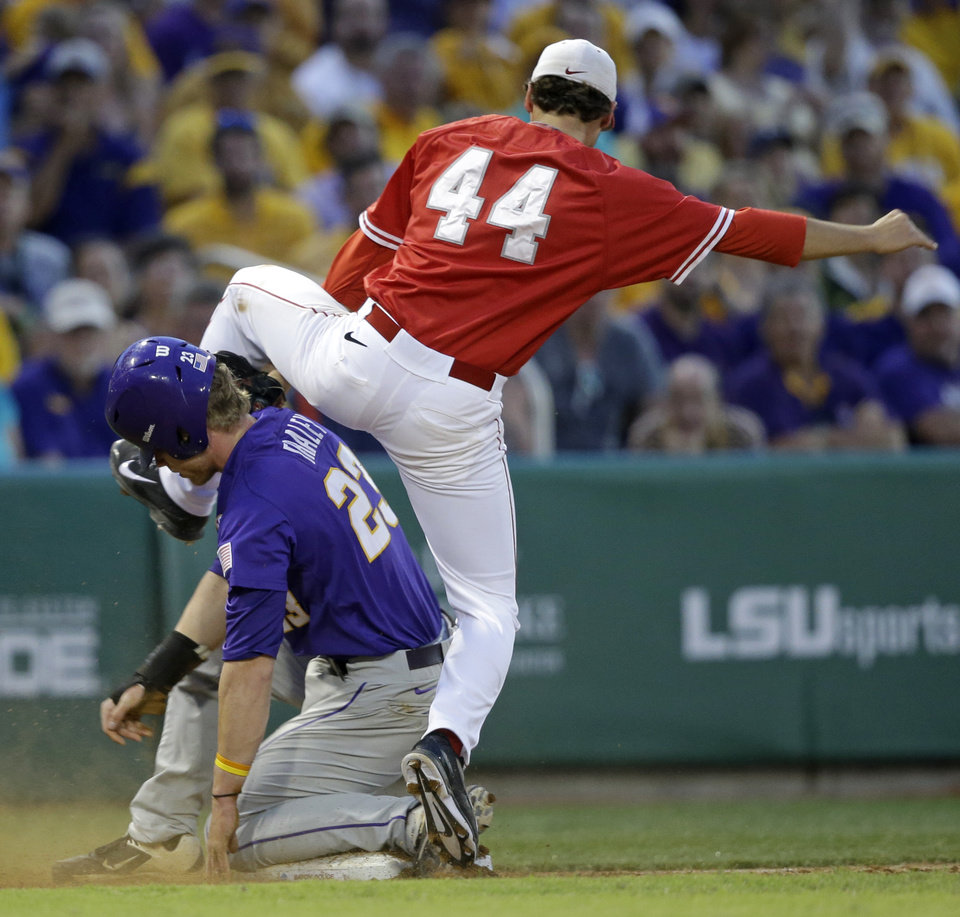 Photo - LSU's Jake Fraley (23) is caught stealing third base by Houston infielder Connor Hollis (44) in the third inning of an NCAA college baseball regional tournament game in Baton Rouge, La., Saturday, May 31, 2014. (AP Photo/Gerald Herbert)