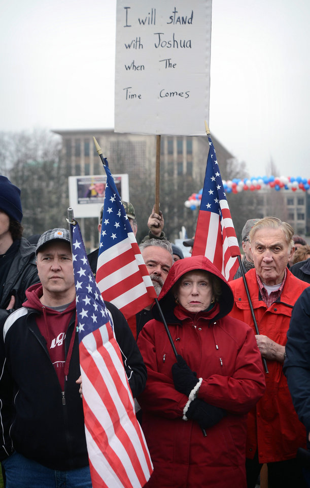 Photo - People hold United States flags during a pro-gun rally at the Washington state Capital in Olympia, Washington on Saturday, Jan. 19, 2013. (AP Photo/The News Tribune, Lui Kit Wong)