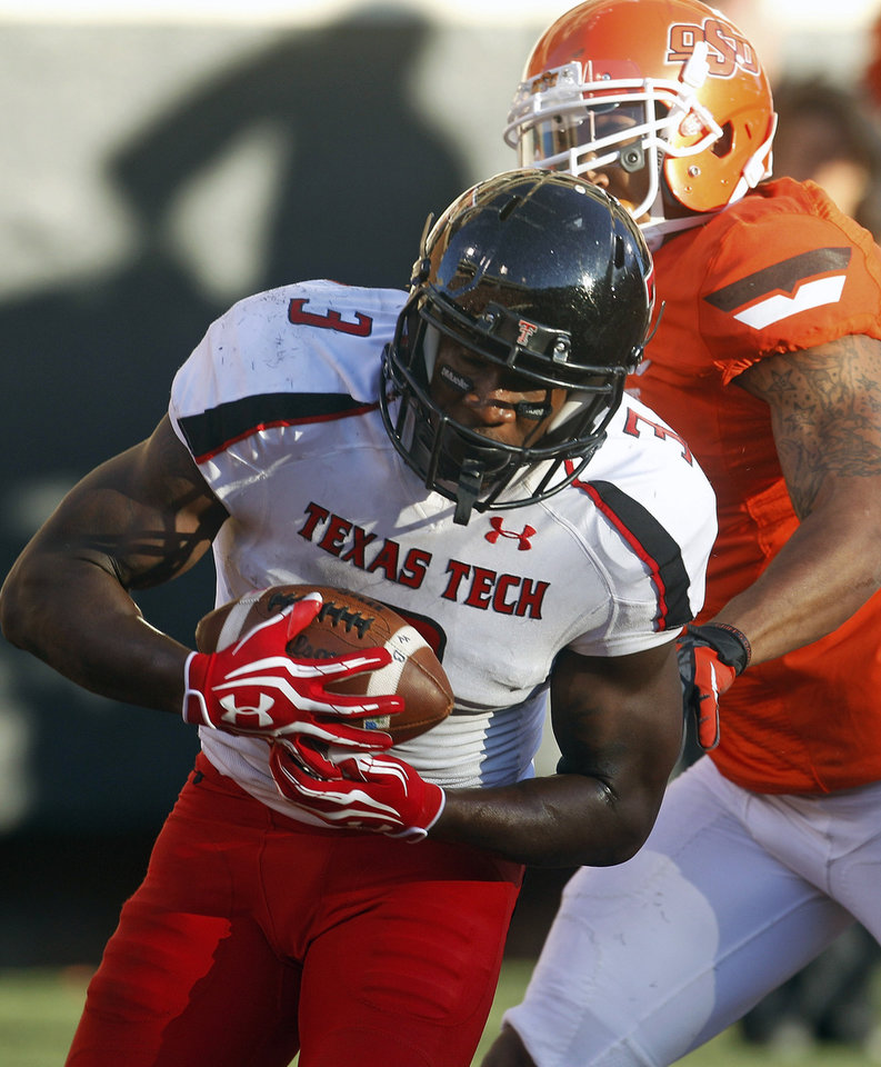 Texas Tech's Tyson Williams (3) catches a pass from quarterback Seth Doege to score in front of Oklahoma State safety Shamiel Gary in the second quarter of an NCAA college football game in Stillwater, Okla., Saturday, Nov. 17, 2012. (AP Photo/Sue Ogrocki)