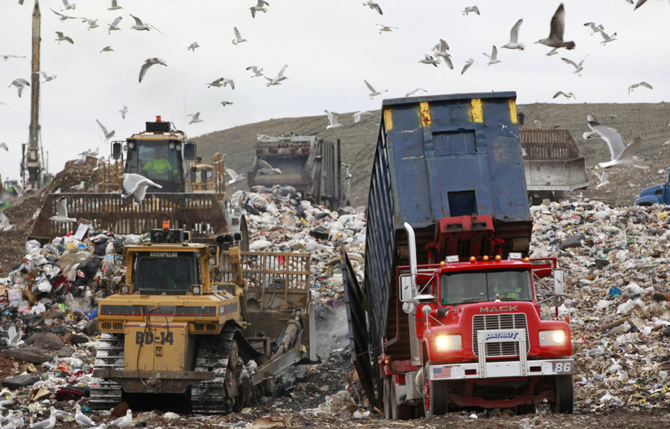 Photo - File -- In this Wednesday, Dec. 14, 2011 file photo a garbage truck, right, empties its load as bulldozers process the waste at the Central Landfill, in Johnston, R.I. The landfill has been operating without a federally required permit for 16 years, according to the Conservation Law Foundation, a top New England environmental group, which has sent a notification indicating it plans to sue under the Clean Air Act. (AP Photo/Steven Senne, File)