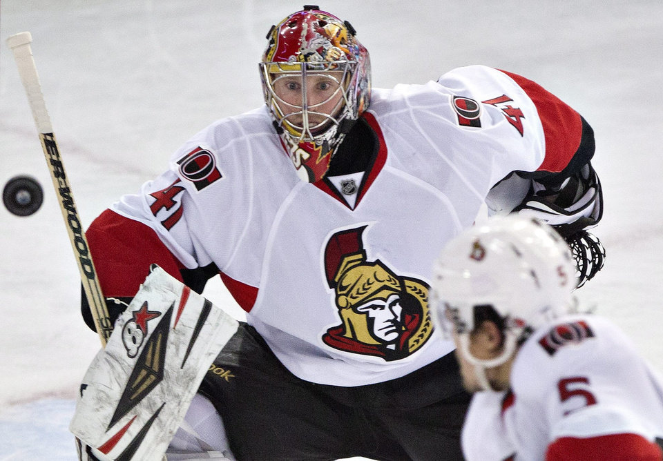 Photo - Ottawa Senators goalie Craig Anderson (41) and Cody Ceci (5) look for the loose puck during the second period of an NHL hockey game, Tuesday, March 4, 2014 in Edmonton, Alberta. (AP Photo/The Canadian Press, Jason Franson)